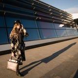 Imagen del oto?o de una mujer joven en la calle Mujer en una capa y un bolso de moda fotos de archivo
