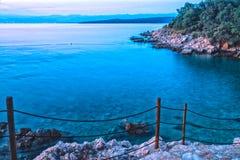 Imagen del paisaje de la puesta del sol de la oscuridad de la playa croata con las escaleras rocosas Fotografía de archivo