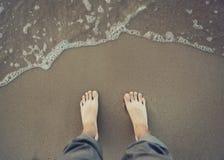 Imagen del pie desnudo masculino cerca de la agua de mar foto de archivo libre de regalías