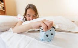 Imagen del primer del adolescente enojado que miente en cama y que apaga el despertador Imagen de archivo libre de regalías