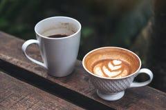 Imagen del primer de dos tazas de café sólo y de latte con arte del latte del corazón en banco de madera en naturaleza verde Foto de archivo libre de regalías