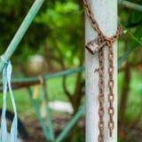 Imagen del primer de la cerradura y de la cadena aherrumbradas en la columna de acero con el fondo borroso del bokeh Concepto del fotos de archivo