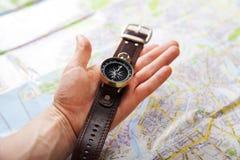 Primer de la mano con el compás magnético sobre un mapa Foto de archivo