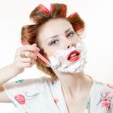 Imagen del primer de la muchacha modela joven hermosa que afeita la cara que parece in camera aislada en el retrato blanco del fo Foto de archivo