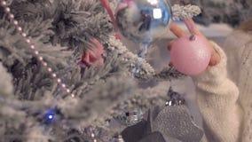 Imagen del primer de la mujer en suéter que adorna el árbol de navidad con las chucherías metrajes