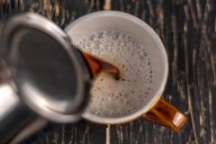 Imagen del primer de las manos masculinas que vierten el concepto del café y del artista y de la preparación de la leche, café de imágenes de archivo libres de regalías