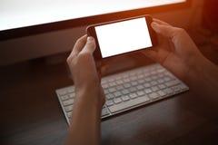 Imagen del primer de las manos que sostienen smartphone con la maqueta en blanco en el fondo del teclado fotografía de archivo