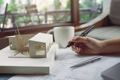 Imagen del primer de los arquitectos que dibujan el papel de dibujo de la tienda con el modelo de la arquitectura imágenes de archivo libres de regalías
