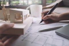 Imagen del primer de los arquitectos que dibujan el papel de dibujo de la tienda con el modelo de la arquitectura imagen de archivo libre de regalías