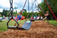 Imagen del primer de un oscilación en un parque para los niños Niños swigning en el fondo foto de archivo libre de regalías