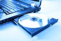 Imagen del primer de una computadora portátil y de un disco del CD/DVD Imágenes de archivo libres de regalías