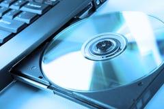 Imagen del primer de una computadora portátil y de un disco del CD/DVD Foto de archivo libre de regalías