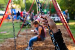 Imagen del primer de una mano de la mujer joven que sostiene una cadena del oscilación en un parque imágenes de archivo libres de regalías
