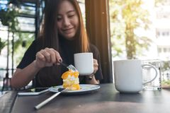 Imagen del primer de una mujer asiática hermosa que come una torta anaranjada mientras que bebe el café Imagen de archivo libre de regalías