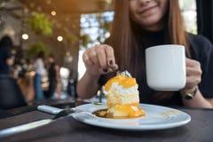 Imagen del primer de una mujer asiática hermosa que come una torta anaranjada mientras que bebe el café Fotografía de archivo libre de regalías