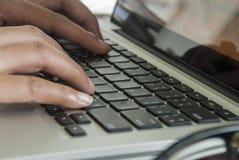 Imagen del primer de una mujer joven que está mecanografiando en un ordenador portátil imágenes de archivo libres de regalías