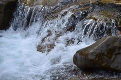 Imagen del primer de una pequeña cascada salvaje bajo la forma de corrientes cortas del agua entre las piedras de la montaña fotos de archivo