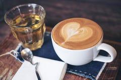 Imagen del primer de una taza de café caliente y de un vidrio del té en la tabla de madera del vintage Imágenes de archivo libres de regalías