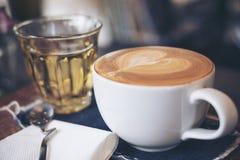Imagen del primer de una taza de café caliente y de un vidrio del té en la tabla de madera del vintage Foto de archivo libre de regalías