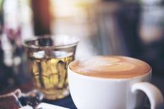 Imagen del primer de una taza de café caliente y de un vidrio del té en la tabla de madera del vintage Fotos de archivo