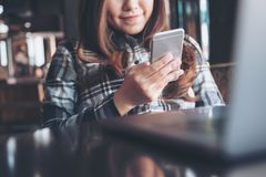 Imagen del primer de una tenencia asiática hermosa de la mujer, usando y mirando el teléfono elegante con el ordenador portátil e Fotografía de archivo