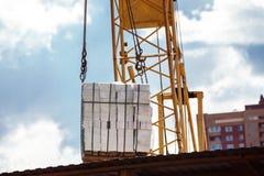 Imagen del primer del montón de elevación de la grúa de ladrillos en el cielo azul Foto de archivo