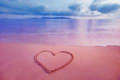 Imagen del primer del símbolo del corazón escrita en la arena en la salida del sol rosada Imagen de archivo