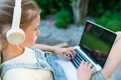 Imagen del primer del vídeo de observación de la chica joven en los wi del ordenador portátil Imagen de archivo