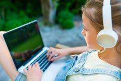 Imagen del primer del vídeo de observación de la chica joven en los wi del ordenador portátil Fotos de archivo libres de regalías