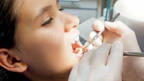 Imagen del primer del dentista que examina los dientes de las muchachas con el espejo y los instrumentos especiales Fotografía de archivo libre de regalías