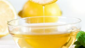 Imagen del primer del goteo de la miel de la rebanada del limón después de sumergirla en tarro Imagenes de archivo