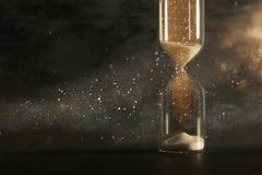 Imagen del reloj de arena como hora que pasa concepto sobre el fondo negro para el plazo del negocio capa del brillo Fotos de archivo libres de regalías