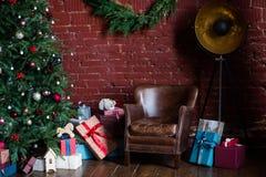 Imagen del sitio con las decoraciones de la Navidad, picea con las decoraciones, butaca de cuero fotografía de archivo libre de regalías