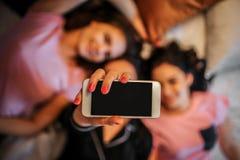 Imagen del teléfono blanco a disposición de una muchacha Ella miente en cama con sus amigos Los modelos sonríen Parecen felices imagenes de archivo