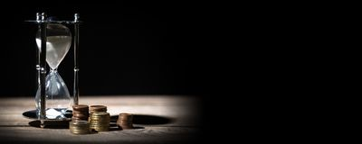 Imagen del tiempo y del concepto del dinero - enarene el reloj y foto de archivo libre de regalías