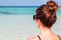 Imagen del tres cuartos de una mujer joven en la playa que mira el mar azul claro imagenes de archivo