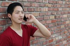 Imagen del varón joven usando el teléfono móvil Imágenes de archivo libres de regalías