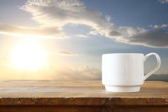 Imagen delantera de la taza de café en la tabla delante de la puesta del sol Imagenes de archivo
