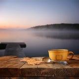 Imagen delantera de la taza de café sobre la tabla de madera delante de la opinión de niebla tranquila del lago en la puesta del  Fotografía de archivo libre de regalías