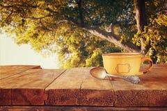 Imagen delantera de la taza de café sobre la tabla y las hojas de otoño de madera delante del fondo del bosque Imagen retra del e imágenes de archivo libres de regalías