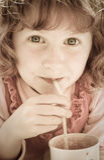 Imagen desaturada de la muchacha del oung con el pelo rojo rizado que bebe a través de una paja fotografía de archivo