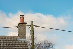 Imagen detallada del par de una cabaña inglesa grande que muestra la estructura del tejado y de la chimenea imagen de archivo libre de regalías