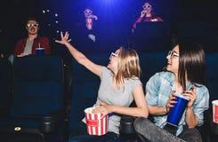 Imagen divertida de las muchachas que se sientan junto en pasillo del cine Están mirando al muchacho que se sienta detrás de ello Fotografía de archivo