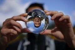 Imagen divertida del hombre asiático a través de una bola de cristal Foto de archivo