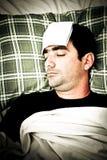 Imagen dramática de un hombre enfermo en cama con fiebre Fotografía de archivo libre de regalías