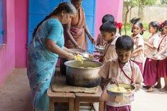 Imagen editorial documental No identificado womaen a los niños del servicio para el almuerzo en la cantina al aire libre Fotografía de archivo