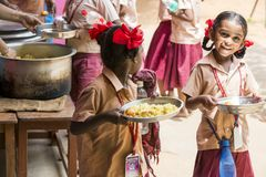 Imagen editorial documental No identificado womaen a los niños del servicio para el almuerzo en la cantina al aire libre Imagenes de archivo