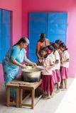 Imagen editorial documental No identificado womaen a los niños del servicio para el almuerzo en la cantina al aire libre Fotos de archivo