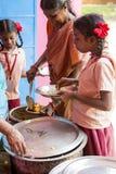 Imagen editorial documental No identificado womaen a los niños del servicio para el almuerzo en la cantina al aire libre Foto de archivo