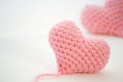 Imagen enfocada de los corazones rosados de un ganchillo en un fondo blanco Fotografía de archivo